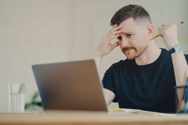 落ち込んだビジネスマンやオフィス ワーカーで、鉛筆を持ち、ノートパソコンのディスプレイを神経質に見て、仕事の結果について強調し、職場でのビジネス上の決定に疑いを持っている