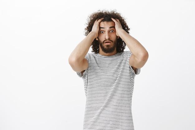 トレンディなストライプのtシャツにアフロのヘアカットをし、頭の上で手をつないで眉毛を持ち上げ、緊張してショックを受けた心配している絶望的な男性フリーランサー