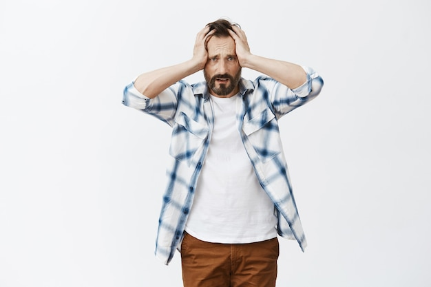 Worried and distressed bearded mature man posing