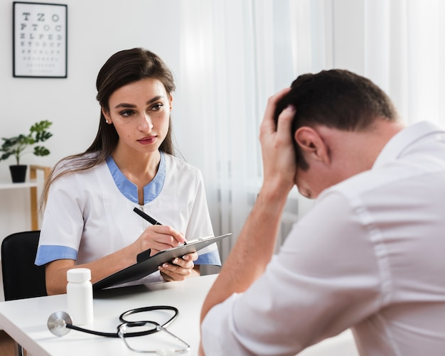 Worried doctor looking at sad patient