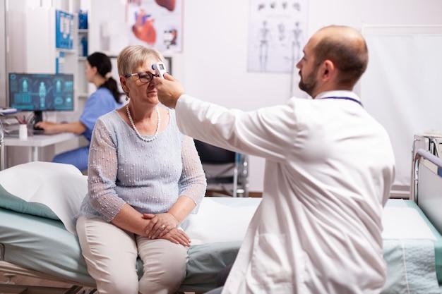 Обеспокоенный врач, измеряющий температуру тела пожилой женщины во время консультации, сидя на больничной койке