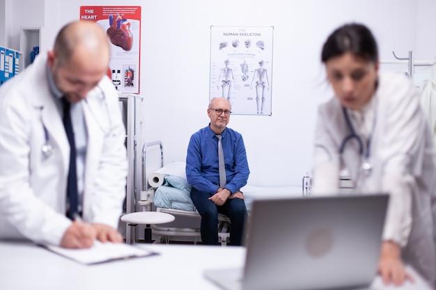 걱정스러운 의사들은 노트북을 사용하여 환자의 건강을 확인하고 노인이 백그라운드에서 기다리는 동안 환자의 결과를 분석합니다. 노트북을 사용하여 동료에게 치료를 보여주고 설명하는 의사
