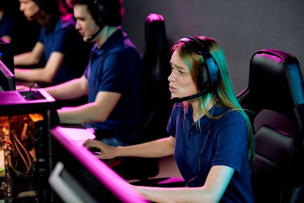 Обеспокоенная девушка киберспорта в гарнитуре с микрофоном играет в видеоигру в компьютерном клубе