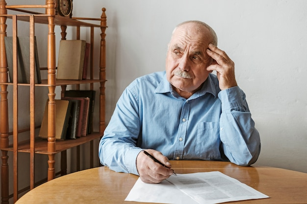 Worried elderly man completing a form