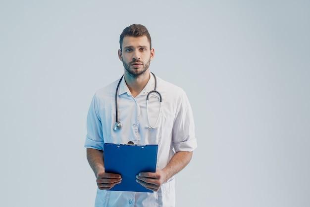Обеспокоенный европейский мужской доктор со стетоскопом и доской сзажимом для бумаги. молодой бородатый мужчина в белом халате. изолированные на сером фоне с бирюзовым светом. студийная съемка. скопируйте пространство.