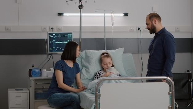 回復中に眠っている間に病気の娘を監視する病気の専門知識について話し合う心配している家族...