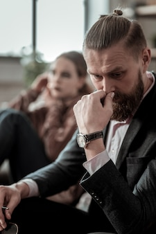 Worried father. close up of bearded father wearing hand watch feeling worried about depression of daughter