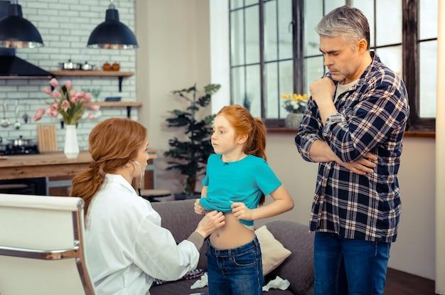 걱정되는 아버지. 그녀의 건강에 대해 생각하는 동안 그의 딸 뒤에 서 심각한 사려 깊은 남자