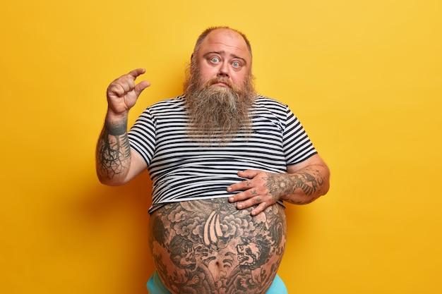 Обеспокоенный толстяк показывает пальцами размер, говорит о чем-то очень маленьком или крошечном, просит подождать несколько минут, держит руку на толстом животе, изолированном желтой стеной. не много, мало