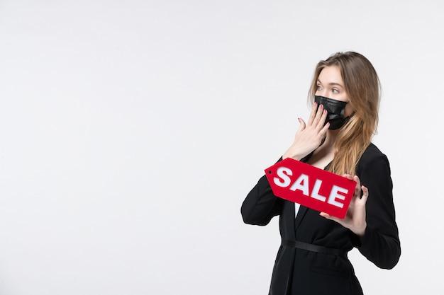 Imprenditrice preoccupata in tuta che indossa la sua maschera medica e mostra la vendita sul muro bianco isolato
