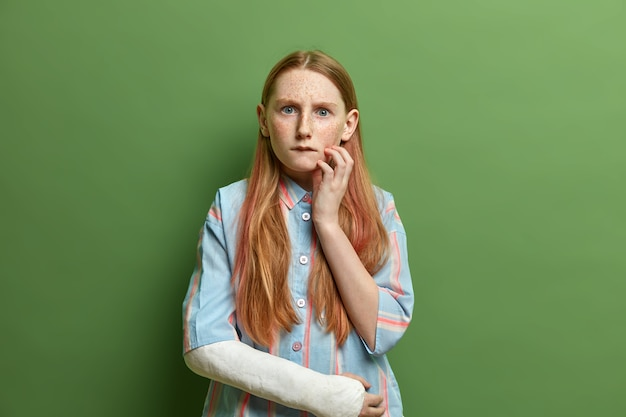 Worried freckled girl bites lips and looks with sullen expression , hears puzzled news, wears shirt and cast on broken arm, has natural beauty, poses indoor. negative emotions concept