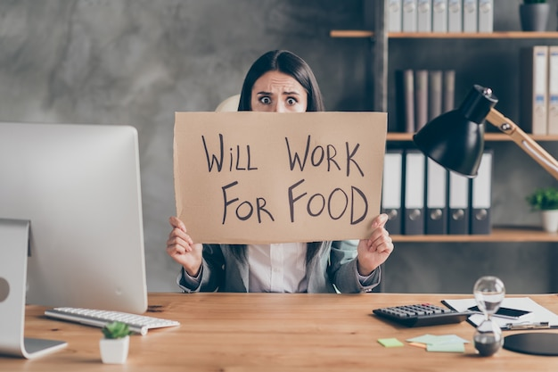 Worried frustrated girl agent marketer economist sit table hold card board text will work for food need job covid crisis staff cut-out dismissal wear blazer jacket in workplace workstation