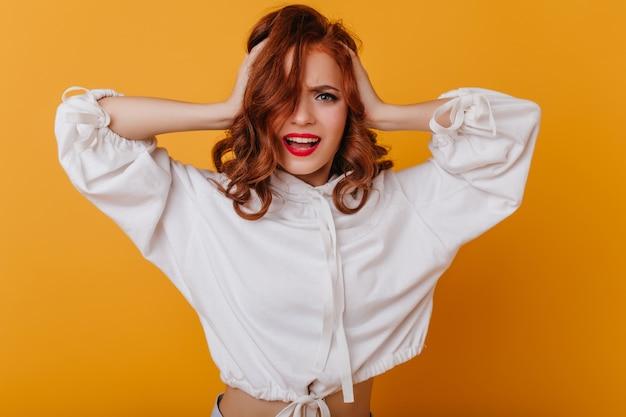 노란 벽에 포즈 붉은 입술으로 걱정 된 생강 여자. 그녀의 머리를 만지고 흰색 스웨터에 감정적 인 여성 모델.
