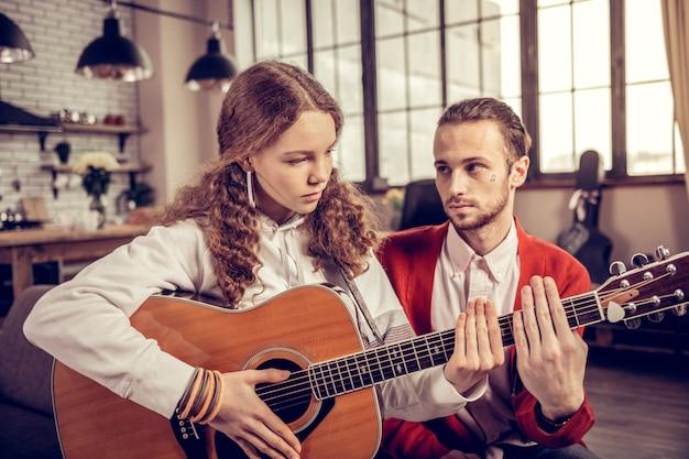 心配している女の子。彼女の家庭教師の近くでギターを弾きながら心配を感じている巻き毛の黒髪の10代の少女
