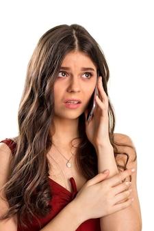 心配している女の子が携帯電話を持っています。濃い赤のドレスとネックレス。緊張しないでください。問題には解決策が必要です。