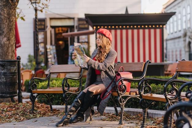 Обеспокоенная девушка в черных кожаных сапогах, глядя на карту, сидя в парке