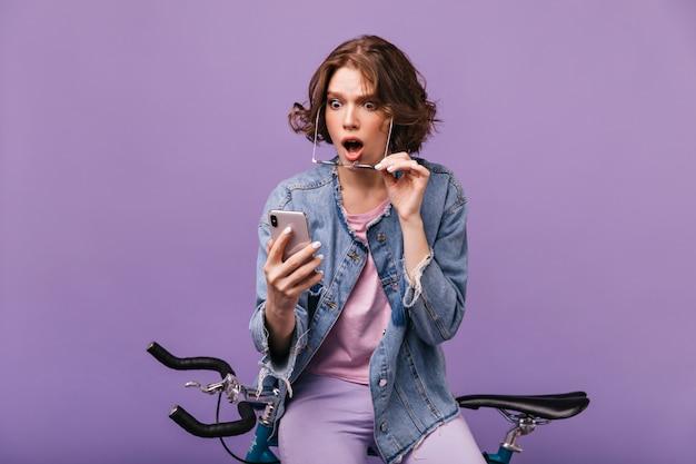 Взволнованная девушка в джинсовой куртке, смотрящей на экран телефона. крытый снимок привлекательной кавказской дамы, сидящей на велосипеде со смартфоном и выражающей изумление.