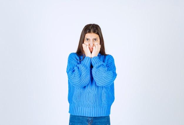 彼女の指を噛んで楽しみにしている暖かいセーターの心配している女の子モデル。