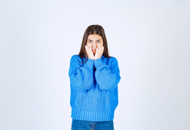 Modello ragazza preoccupata in maglione caldo che si morde le dita e guarda avanti.