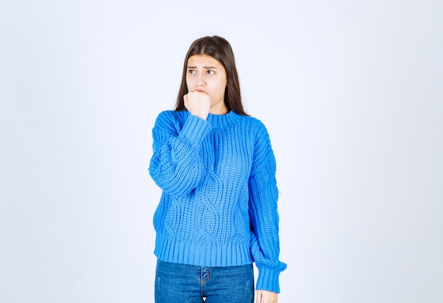Worried girl model in warm sweater biting her fingers and looking forward.