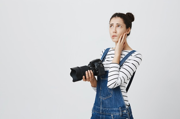 緊張している心配している女の子の写真家。カメラを保持している女性と動揺を感じる