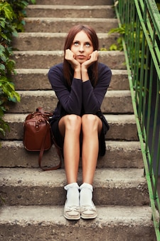 Worried girl sitting on stone stairs