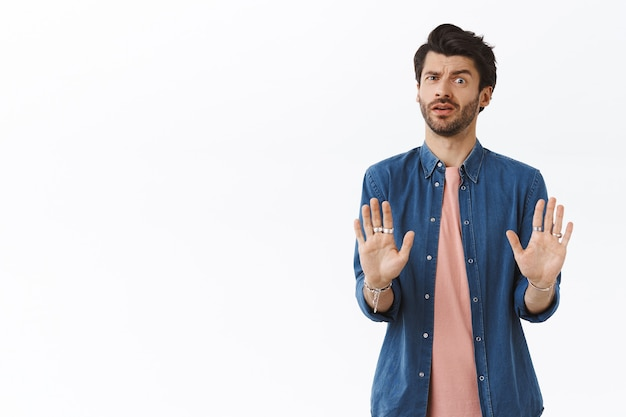 Worried guy doesnt like how offer sounds, trying avoid bad affairs, shaking hands in no reply, rejecting or refusing something suspicious and awful, cringe from aversion or dislike, white wall