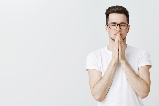 Worried guy in glasses holding hands in pray, pleading