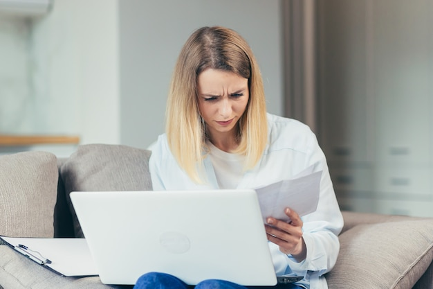 걱정되는 주부는 집에서 소파에 앉아 일과 월 소득에 좌절하면서 과장된 청구서를 지불합니다.