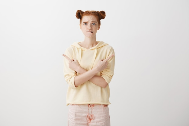 Worried and indecisive redhead girl biting lip anxious, pointing fingers sideways at two choices