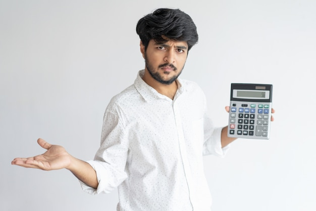 Worried indian business man holding and showing calculator