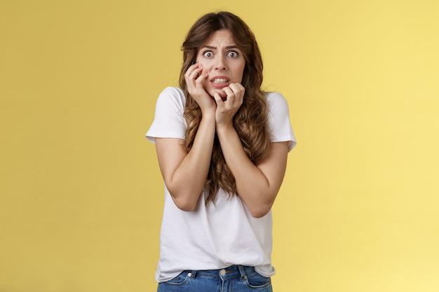 Обеспокоенная неуверенная в себе нервная европейка кусает ногти, смотрит в камеру, в тревоге, в панике трогает щеку тим ...