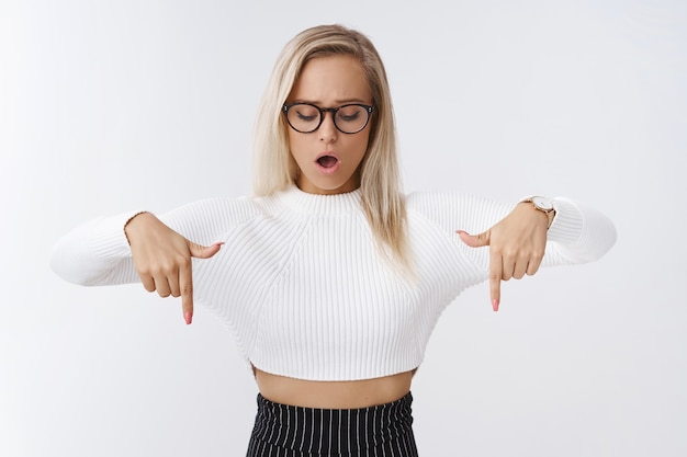 Worried and intense beautiful female in glasses cropped sweater complaining standing nervous and questioned looking pointing down suspicious thing downwards at bottom over white background.