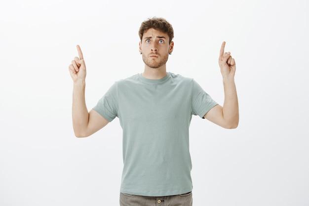 Обеспокоенный напряженный веселый светловолосый парень в футболке, показывающий вверх поднятыми указательными пальцами и смотрящий на небо с тревожно-испуганным выражением лица, беспокоясь за ребенка на детской площадке