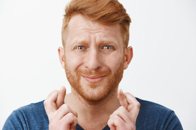 Worried intense redhead miserable guy with beard in blue t-shirt crossing fingers, pursing lips and frowning while feeling nervous and begging for good luck and fulfillment of wish