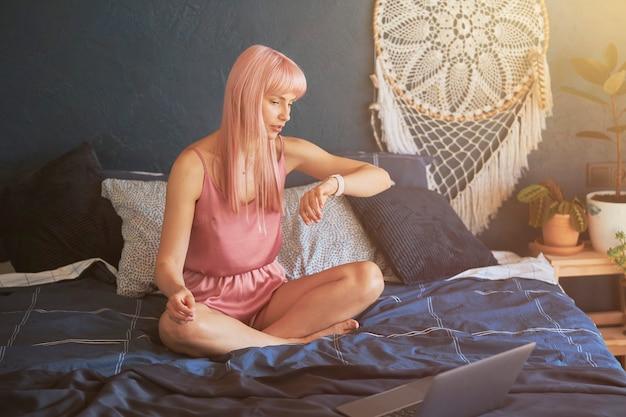 긴 분홍색 머리를 한 걱정스러운 여성이 큰 침대에 앉아 있는 스마트워치에서 시간을 확인합니다.