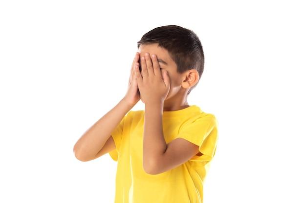 白い背景で隔離の黄色のtシャツを怒らせて心配しているラテンの少年