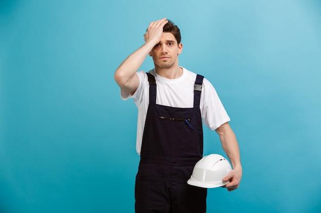 青い壁にheadfに触れながら保護用のヘルメットを保持している心配している男性ビルダー