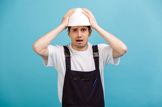 青い壁に頭を抱えている間保護用のヘルメットで心配している男性ビルダー