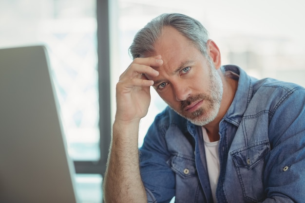 Worried male executive sitting in office
