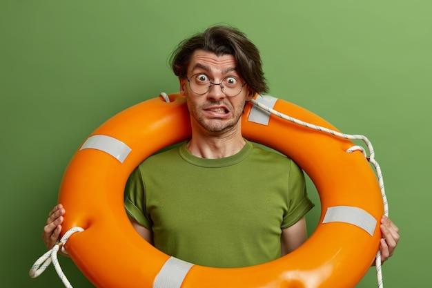 心配している男性の救助者は歯を食いしばって困惑しているように見え、水泳安全装置でポーズをとり、ゴム製の救命具を運び、立っています