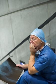 Обеспокоенный хирург-мужчина держит рентгеновский снимок на лестнице