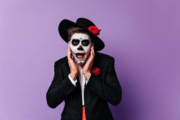 Обеспокоенный мужчина в традиционном мексиканском костюме позирует в день мертвых. студийный портрет удивленного парня зомби в черной шляпе.