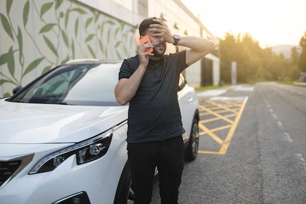 Обеспокоенный мужчина звонит по телефону, пока закрывает глаза рукой после поломки автомобиля. носит черную одежду. белая машина припаркована у дороги