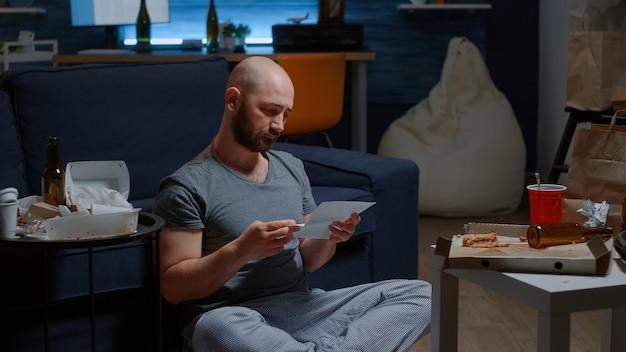 걱정된 남자 은행에서 편지를 읽고 경고 문서 열기