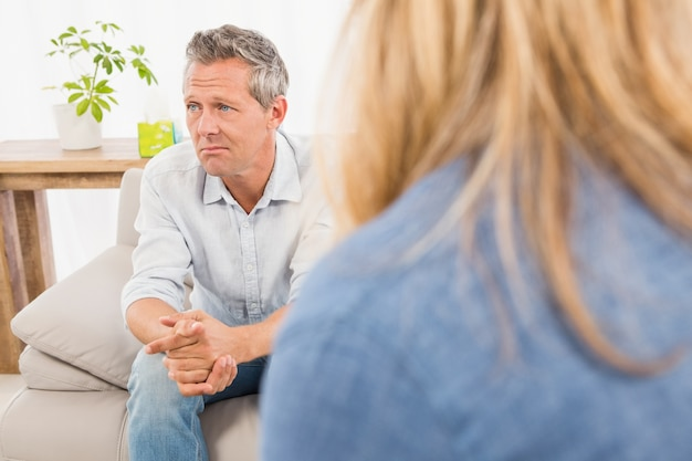 Worried man sitting on couch and talking to therapist