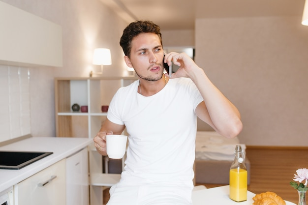 Worried man in white t-shirt talking on phone holding cup of tea in kitchen