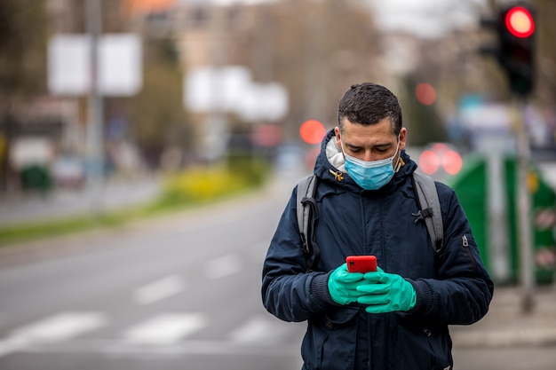 Worried man with mask checking phone on street