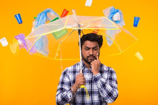 Worried man with transparent umbrella under plastic rain