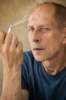 Worried mature man sitting, smoking and thinking about something